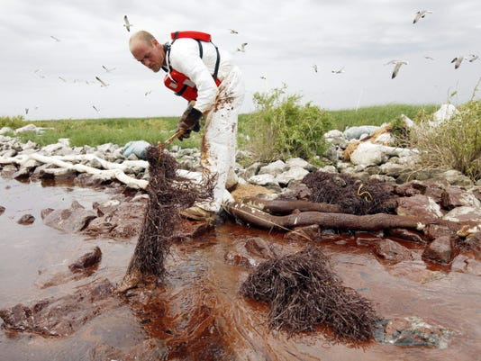 FILE- In this June 4, 2010 file photo, a worker picks up blobs of oil with absorbent snare on Queen Bess Island at the mouth of Barataria Bay near the Gulf of Mexico in Plaquemines Parish, La. BP and five Gulf states announced a record 18.7 billion settlement Thursday, July 2, 2015,  that resolves years of legal fighting over the environmental and economic damage done by the energy giant's oil spill in 2010.