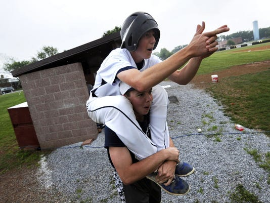 """Members of the West York High School have fun in the midst of a rain delay by participating in """"war games"""" with their opponents from Daniel Boone High School during a Class AAA District 3 baseball tournament game on May 18."""