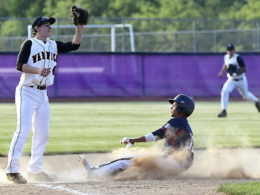Carlin Christian (13) of Chambersburg slides into third as Warwick's Luke Mariano (6) looks to make a tag during the District 3-AAA baseball semifinal on Tuesday. Christian reached base four times to help the Trojans beat Warwick, 6-1.