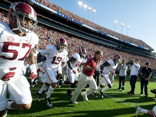 Alabama head coach Nick Saban leads his team onto the