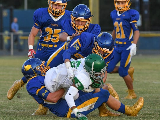 Wren junior Johnathan Cobb (34), left, and Harrison Morgan tackle Easley's Cavario Cureton (5) during the first quarter at Wren High School in Piedmont on Friday.