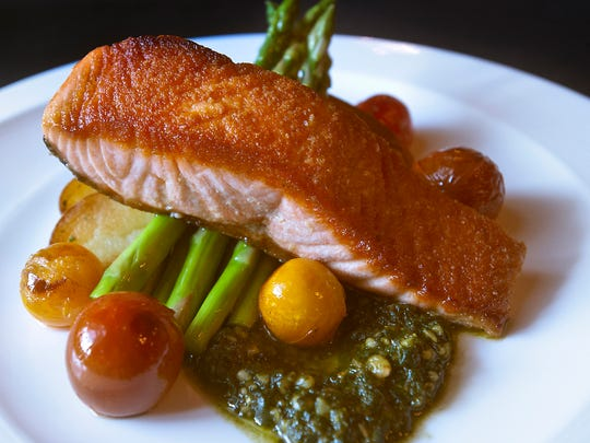The Brown Hotel's pan seared Verlasso salmon is served with spring asparagus, fingerling potatoes, blistered colorful tomatoes and pesto (made from fresh basil Parmigiano-Reggiano cheese, garlic, olive oil and pine nuts).  Feb. 23, 2018