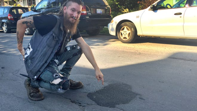 Jason Cockram points to a pothole that he and his friends patched themselves on Lumpkin St, in Hamtramck on Monday, July 27,2015.