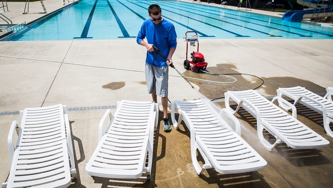 Ben Bullock power washes furniture at Tuhey Pool Tuesday in preparation for the pool's Saturday opening.