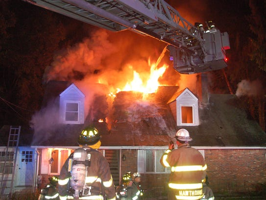 Firefighters look on as flames shoot out of a Hawthorne