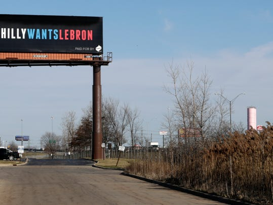One of three billboards trying to entice Cleveland Cavaliers' LeBron James to come to Philadelphia are shown near a highway, Tuesday, Feb. 27, 2018, in Cleveland. The three billboards were unveiled on Monday on busy Interstate-480 outside Cleveland, and each contains a message asking James to sign with the Sixers this summer as a free agent. Although James may not see the signs because they're not on any route he would take from his home in Bath, Ohio, to Quicken Loans Arena, the three-time champion was warmed by their sentiment. (AP Photo/Tony Dejak)
