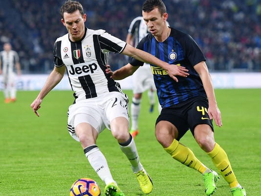 Juventus' Stephan Lichtsteiner, left, is challenged by Inter Milan's Ivan Perisic during a Serie A soccer match at the Juventus Stadium in Turin, Italy, Sunday, Feb. 5, 2017. (Alessandro Di Marco/ANSA via AP)