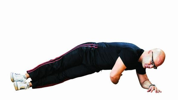 """Trainer Chuck Shelton demonstrates the second position of the """"side plank with rotation"""" exercise at the Clinton YMCA."""