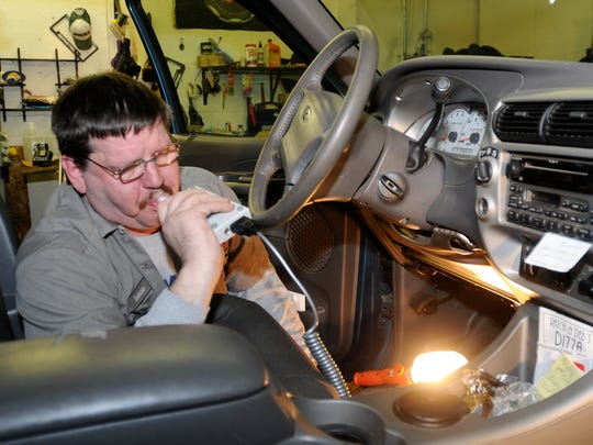 Ron Sienkierke, a technician at Extreme Clean Automobile Detailing in Oshkosh, tests an ignition interlock device after installing it in a car.