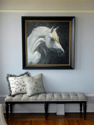 A tufted bench sits under a painting of a horse head in the living room at the condo of Sharon Epps and Alex Fleming in The Commodore.