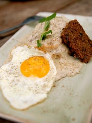 Biscuits and goetta gravy with a sunny side up egg