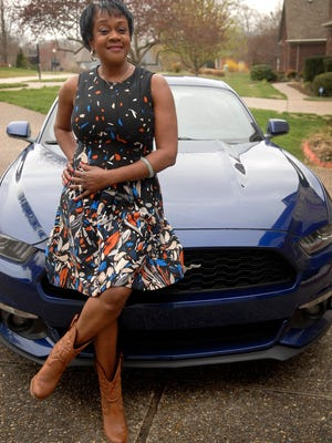"""Lisa W. Jones poses in front of her 2015 Ford Mustang. """"It was my dream car and sort of a mid-life crisis,"""" she said with a smile."""