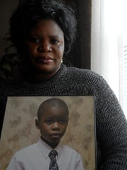 Magdalene Lawson poses with a photograph of her son,