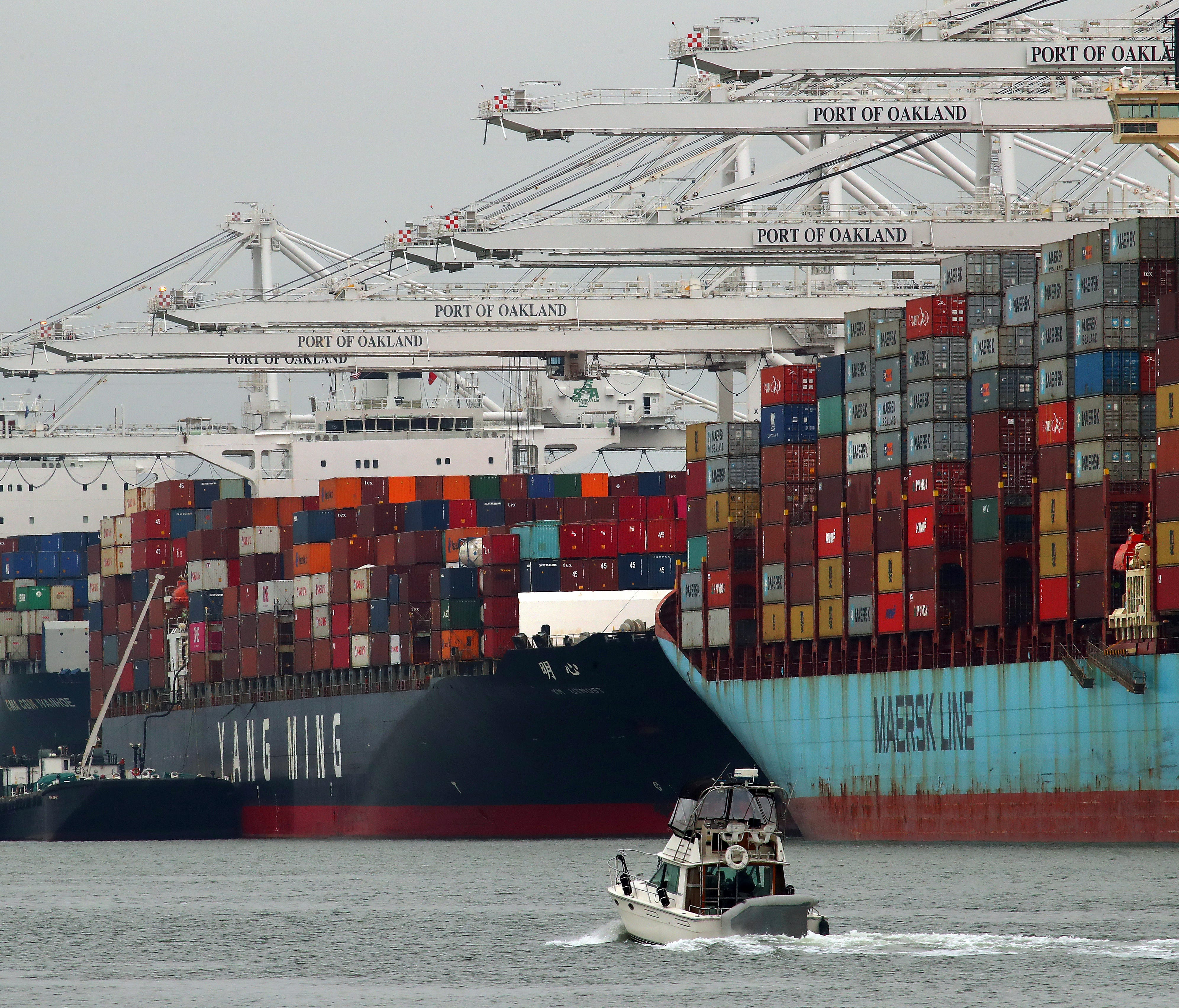 In this July 2, 2018, photo container ships are unloaded at the Port of Oakland in Oakland, Calif. On Friday, July 6, the Commerce Department reports on the U.S. trade gap for May.