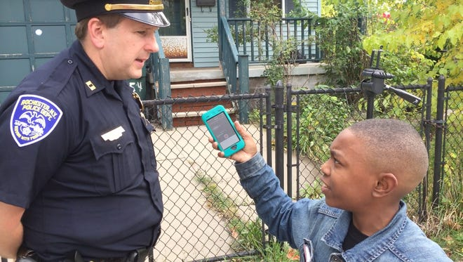 Geoffery Rogers, in eighth grade at Monroe High School, calls himself Rochester's youngest reporter.  He was interviewing Capt. Korey Brown, Rochester police,  about a shooting.