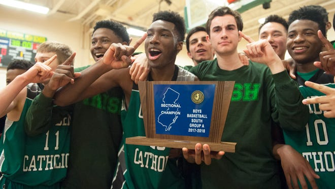 Members of the Camden Catholic boys basketball team celebrate with their trophy after Camden Catholic beat St. Joseph Metuchen, 44-39, in the Non-Public A South boys basketball final played at Brick Township Memorial High School on Thursday.