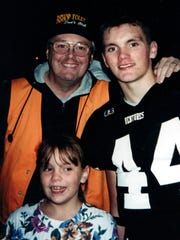 Ken Smith (left) was active at Bishop Foley, where his sons played football. At right is Dave Smith. In front is Julianna Smith, who went to Farmington Hills Mercy.