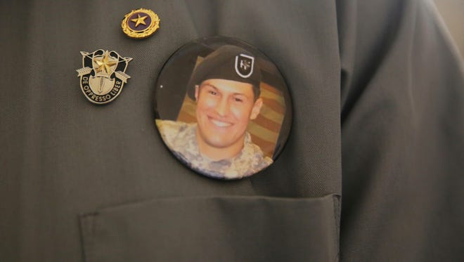 A badge with a photo of Sgt. Matthew Lewellen, a slain U.S. Army Green Beret, is shown pinned to the chest of his father, Charles, in Amman, Jordan, Monday, July 17, 2017. A Jordanian military court convicted a Jordanian soldier of killing Lewellen and two other U.S. military trainers at a Jordanian air base last year. The defendant was sentenced to life in prison with hard labor.