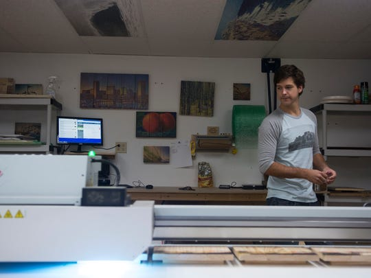 Wyatt Harrison watches as his printer completes multiple photos at once.
