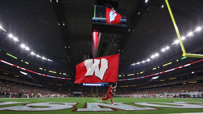 A Wisconsin flag is carried across the filed during the second half of an NCAA college football game Sept. 5 in Arlington, Texas.