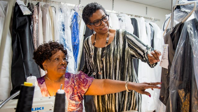 Sandra Spencer, right, owner of Sandra G's alterations shop in Knoxville, looks at garments with seamstress Andrea McBeth.