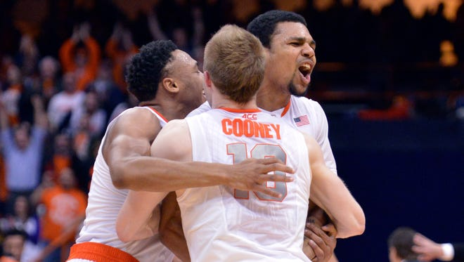 Syracuse guard Michael Gbinije (center) is hugged by teammates Ron Patterson (left) and Trevor Cooney after Gbinije scored the winning basket  Tuesday night