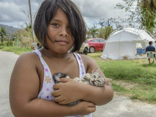 Leinani, 8, carries a kitten outside her Red Cross temporary shelter in Dan Dan, Saipan on Aug. 13 following Typhoon Soudelor. Leinani's family has gone without a reliable source of food and water in the eleven days since the storm.