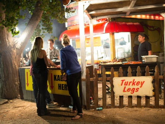 Campers buy late night food at a barbecue vendor in