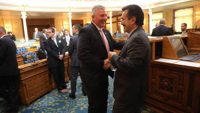 Assemblyman David Rible and Assembly Speaker Vincent Prieto shake hands on the Assembly floor following the vote to raise New Jersey's gas tax on Friday, Oct. 7, 2016.