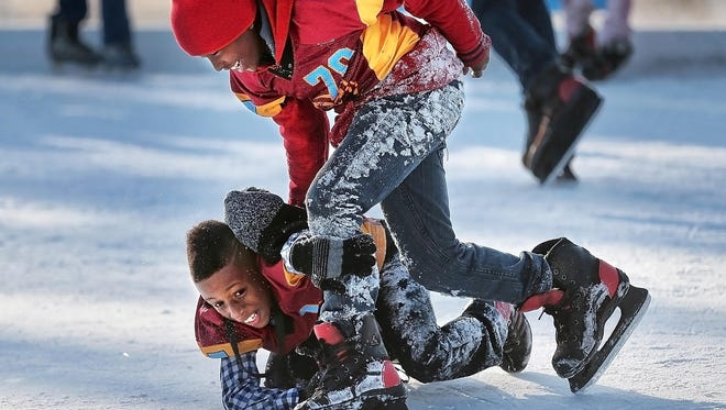 Kenny Garrett tries to tackle Eugene Griffin on the ice to get his hat back at the new Fourth Bluff Ice Rink which opened Saturday at Mississippi River Park.