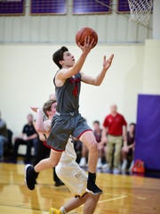 Going to the rim for Divine Child is Parker LePage (4). He scored 13 points for the Falcons against PCA.