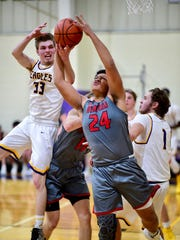 Battling for a rebound Tuesday are Plymouth Christian's Matt Malcolm (33) and Divine Child's Aeron Latham (24). At right for the Eagles is James Fadden (1).
