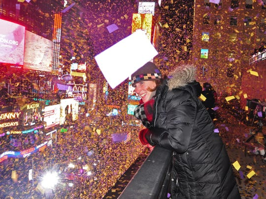 On New Year's Eve, Frankie Suzanne Garr enjoys the scene from a building ledge high above Times Square where she and other volunteers throw confetti on revelers below.  (The large white object in center of photo is a piece of confetti.)