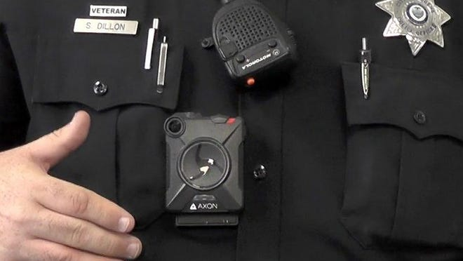 Eugene Police officer Sean Dillon demonstrates one of the department's new body cameras (center).