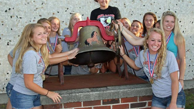 Members of Westfall's softball team rings the school's victory bell after a community celebration in 2014 commemorating their Division III state title at the school.