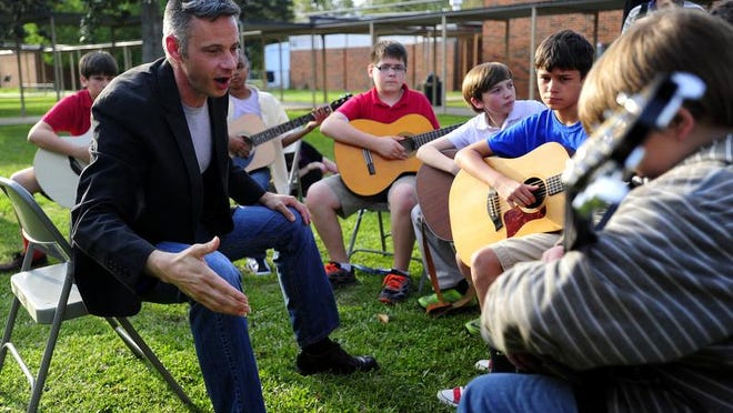 Jasin Muffoletto of Louisiana Classical Guitar Society teaches classical guitar techniques to students during the Guitar Family Jam at L.J. Alleman Middle School in Lafayette, LA, Tuesday, April 1, 2014.   Paul Kieu, The Advertiser