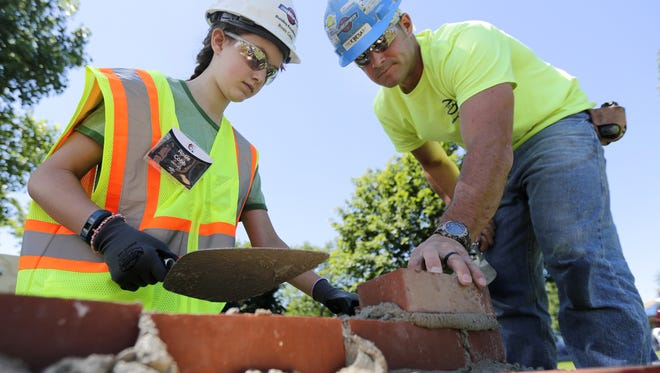 """Journeyman bricklayer Nick Besaw works on a wall with Rosie Cobb during the """"Build Like a Girl"""" event on Friday at Miron Construction Co. in Fox Crossing."""