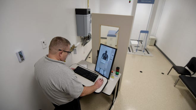 Richland County Jail administrator Capt. Chris Blunk demonstrates how to operate the body scanner at the Richland County Jail.