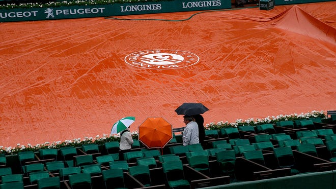 People wait in the stands of Court Philippe Chatrier as the start of day 9 is delayed due to rain at the French Open on May 30.