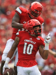 Louisville's Jaire Alexander gets some celebration congratulation from teammate Keith Kelsey after Alexander recovered a Florida State fumble that led to another Cardinal touchdown in the second quarter as Louisville routed the Seminoles 63-20 Saturday afternoon.
