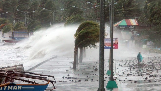 A resident, right, walks past high waves pounding the sea wall amid strong winds as Typhoon Haiyan hit the city of Legaspi, Albay province, south of Manila, on Nov. 8, 2013.