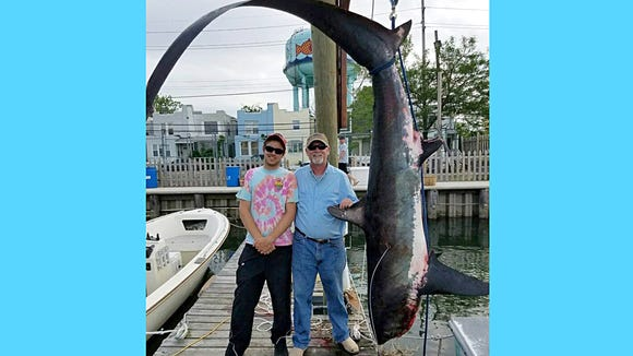 """The Devone family landed this 356 pound thresher shark while fishing on their boat """"Titan."""""""