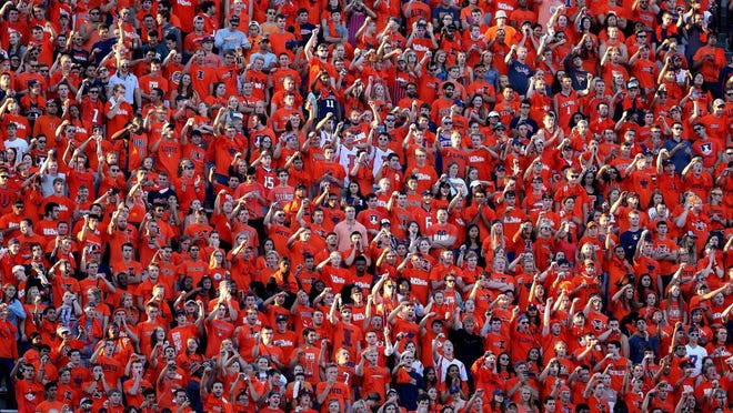 Illinois fans cheer at the start of a game at Memorial Stadium in Champaign. Fans this year won't be able to attend, but can purchase cutouts to sit among the seats.