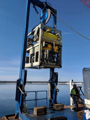 A remotely operated vehicle is prepared to be placed in the Straits of Mackinac to look at utility cables damaged by a ship's anchor.