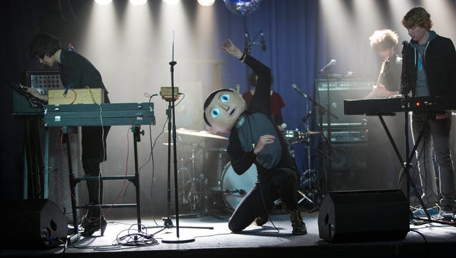 "Frank (center, Michael Fassbender) rocks out with his avant-garde band in the musical comedy ""Frank."""