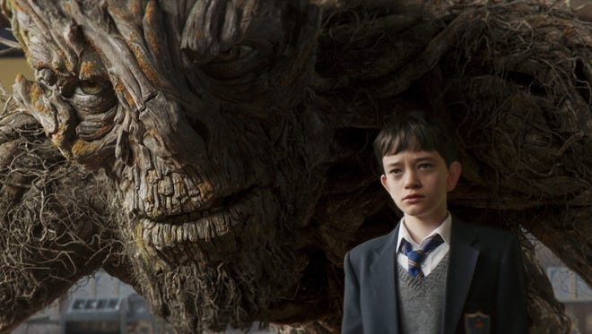"""This image released by Focus Features, Lewis MacDougall appears with The Monster, voiced and performed by Liam Neeson, in a scene from """"A Monster Calls."""" (Focus Features via AP)"""