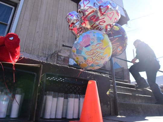 Balloons and candles outside the house at 87 Auburn St. in Paterson where a teenager was killed Saturday.