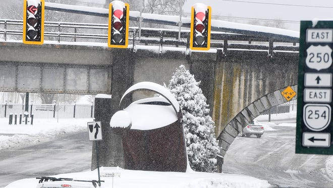 Snow covers the giant watering can in downtown Staunton during a spring snow storm on Wednesday, March 21, 2018.
