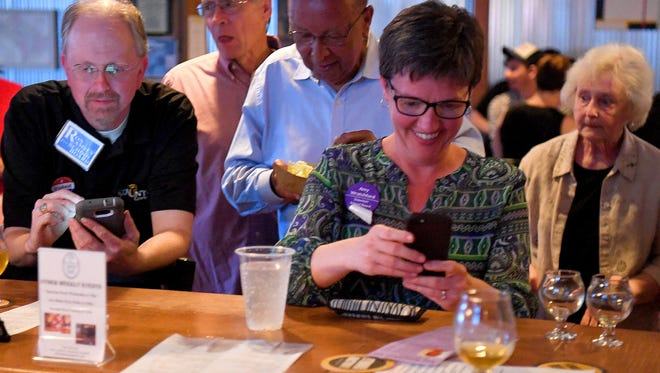 Ron Ramsey, member of the Staunton City School Board, joins school board candidates Kenneth Venable and Amy Wratchford both check their phones as final results are reported. Both attend an election night watch gathering at Redbeard Brewing Company in Staunton on Tuesday, May 1, 2018.  Although Ramsey did not win re-election, both Venable and Wratchford were among those winning seats on the board.