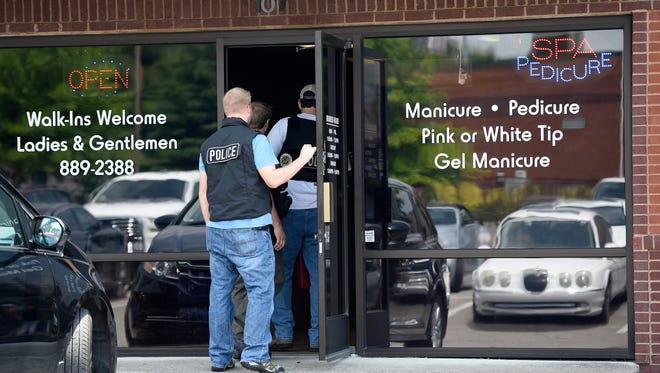Nashville Police personnel enter Shine Nails in Donelson to gather evidence during a raid in connection with an ongoing prostitution, money laundering and human trafficking investigation.